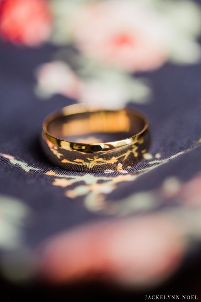 Men's wedding wedding band on floral tie by Jackelynn Noel Photography