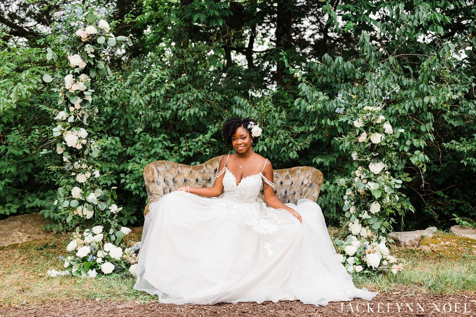 Bride in off the cascading shoulder dress sitting on a green seat surrounded by flowers.
