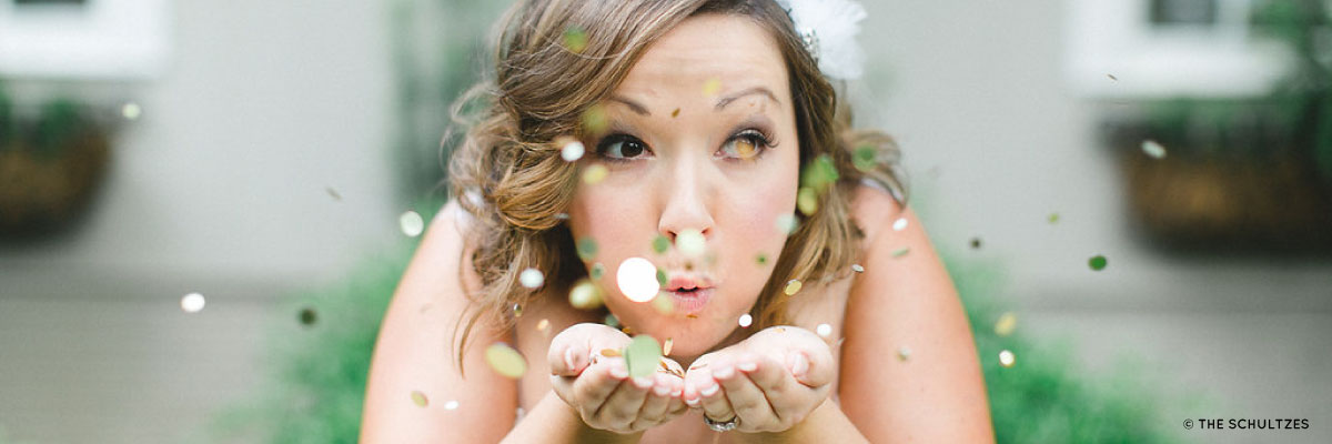 Bride blowing confetti