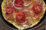 campari tomatoes, lox, red onion and herbs on top of a cream cheese frittata