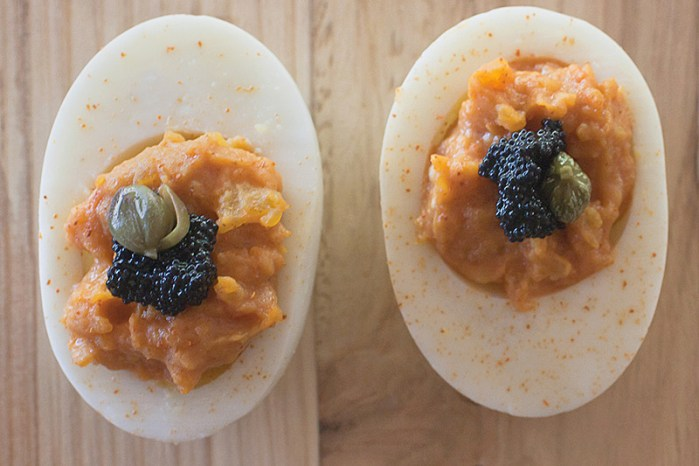 chipotle deviled eggs topped with caviar and capers and sprinkled with chile