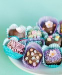 chocolate dipped brownie bites decorated with different kinds of pastel sprinkles served in paper liners to look like boxed chocolates