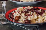 red wine simmered sausages served over a platter of creamy cheesy noodles