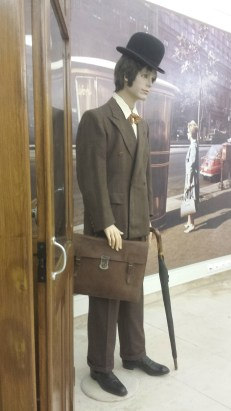 A male Museum Mannequin, waiting patiently by a phone booth.