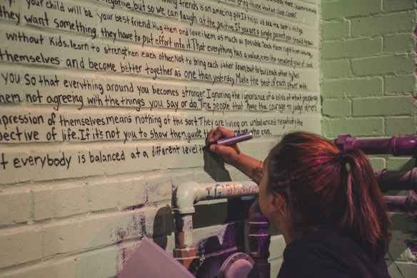 woman holding marker writing on wall