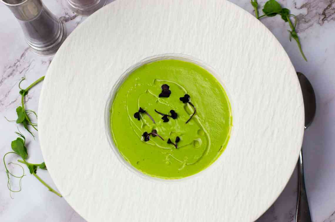 Pea soup with white truffle oil in a white bowl garnished with micro herbs