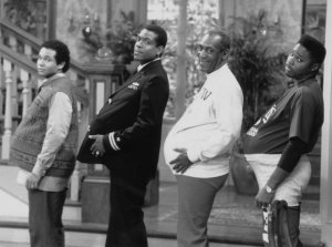 """THE COSBY SHOW -- """"The Day the Spores Landed"""" Episode 8 -- Air Date 11/09/1989 -- Pictured: (l-r) Geoffrey Owens as Elvin Tibideaux, Joseph C. Phillips as Lt. Martin Kendall, Bill Cosby as Dr. Heathcliff 'Cliff' Huxtable, Malcolm-Jamal Warner as Theodore 'Theo' Huxtable (Photo by NBC/NBCU Photo Bank via Getty Images)"""