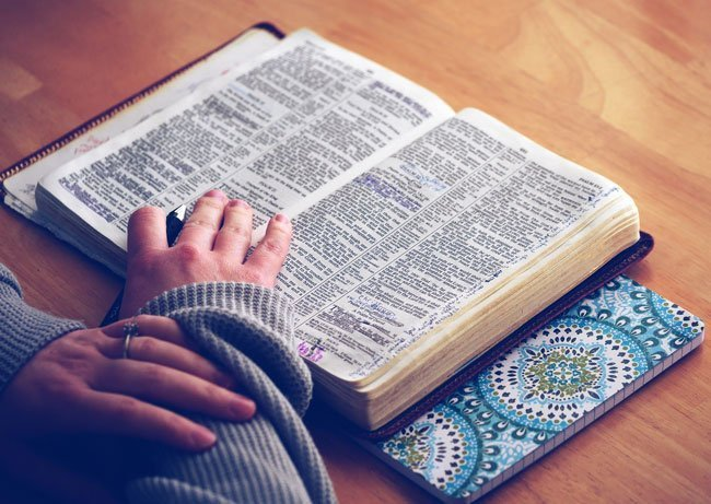 woman studies bible as evidence of a god
