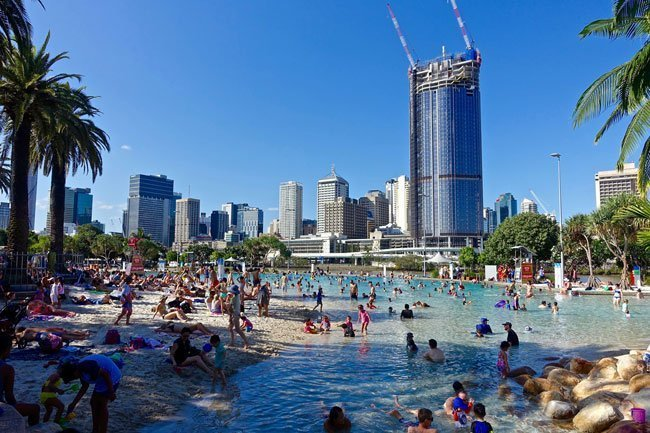 Man-made beach in South Bank in Brisbane, Australia filled with families enjoying the pools in front of  the city backdrop.