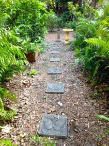 Front yard with stepping stones and edged with plantings.