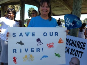 Pam Joy hold a sign SAVE OUR RIVER.