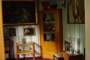 Szafa odznaczeń i medali. Na stoliku pamiątkowy kryształowy wazon z huty Julia