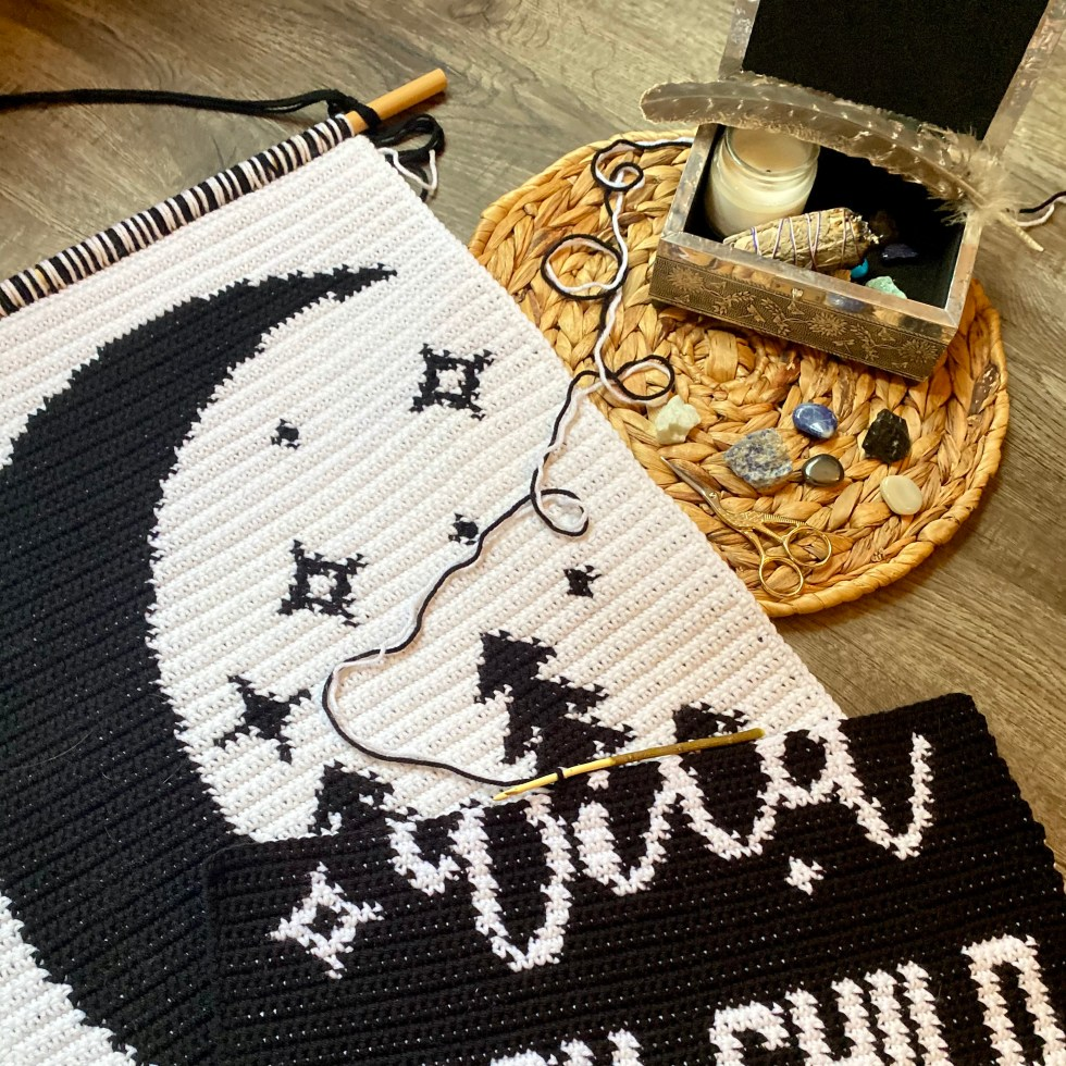 Tapestry crochet patterns in progress. Crystals, candle, smudge stick, and feather sit in and around a keepsake box.