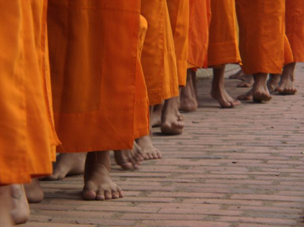 monks feet walking on path by Jade Jackson