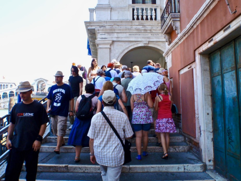Crowds of tourists crossing a bridge in Venice. Image by travel photographer, Jade Jackson.