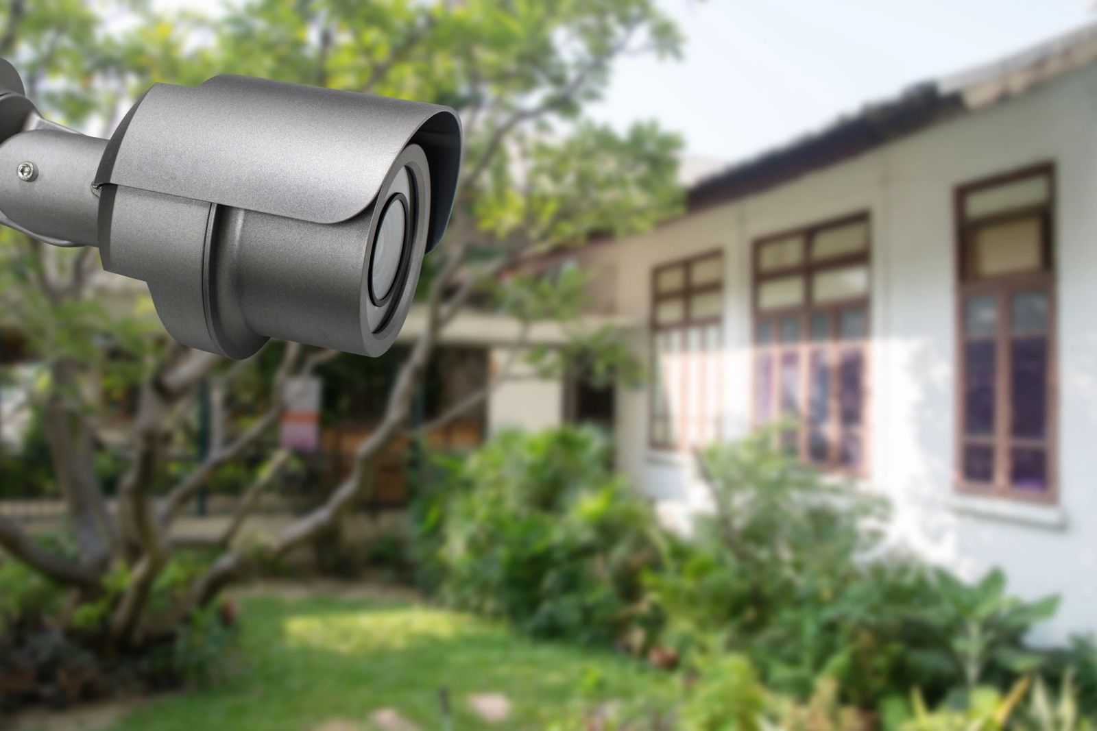 Black home security camera looks over the exterior of a property