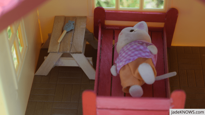 A small white Calico Critter cat rests in a red popsicle stick bed. Beside her, a popsicle stick side table holds a small plastic fish for snacking.