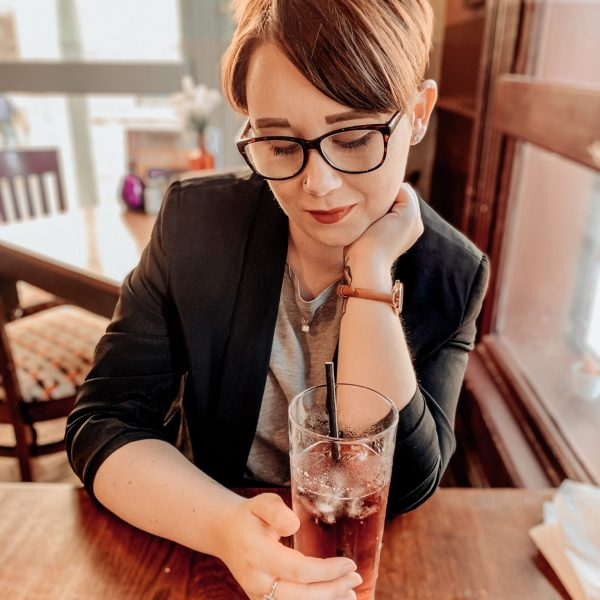 Jade Marie wearing a black blazer, grey top and red lipstick, looking down into a glass of cider