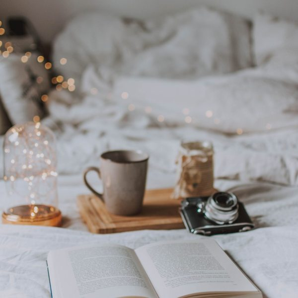 a cup, and open box, a camera and some fairy lights resting on a bed with white bedding
