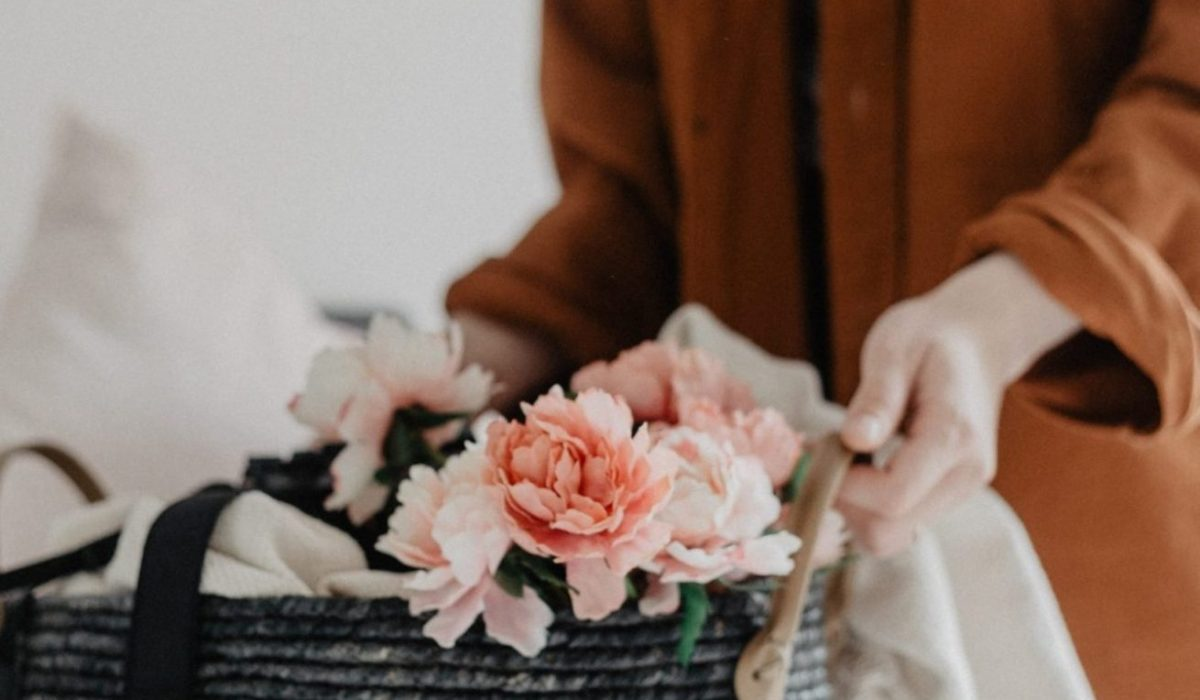 A woman in a brown blazer holing a woven basket with has a camera and some pale pink flowers in it, as well as a blanket at the far side
