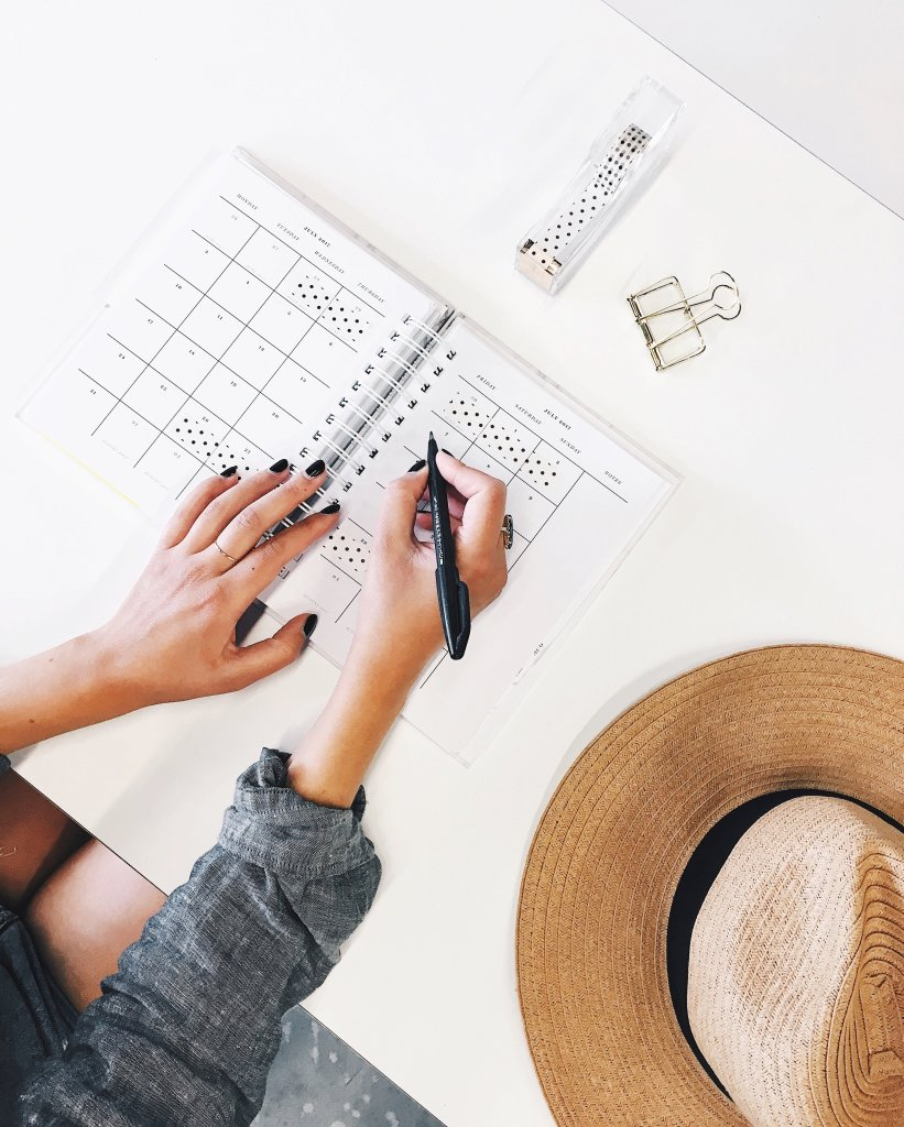 Woman working at a desk. straw hat to the side. stationary and planner nearby