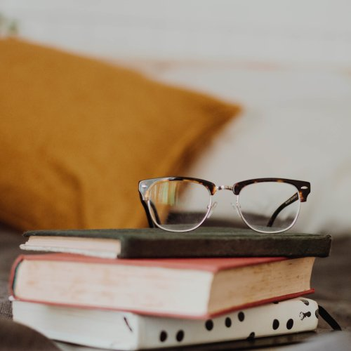 a pair of glasses sat on a pile of books with a yellow cushion in the background