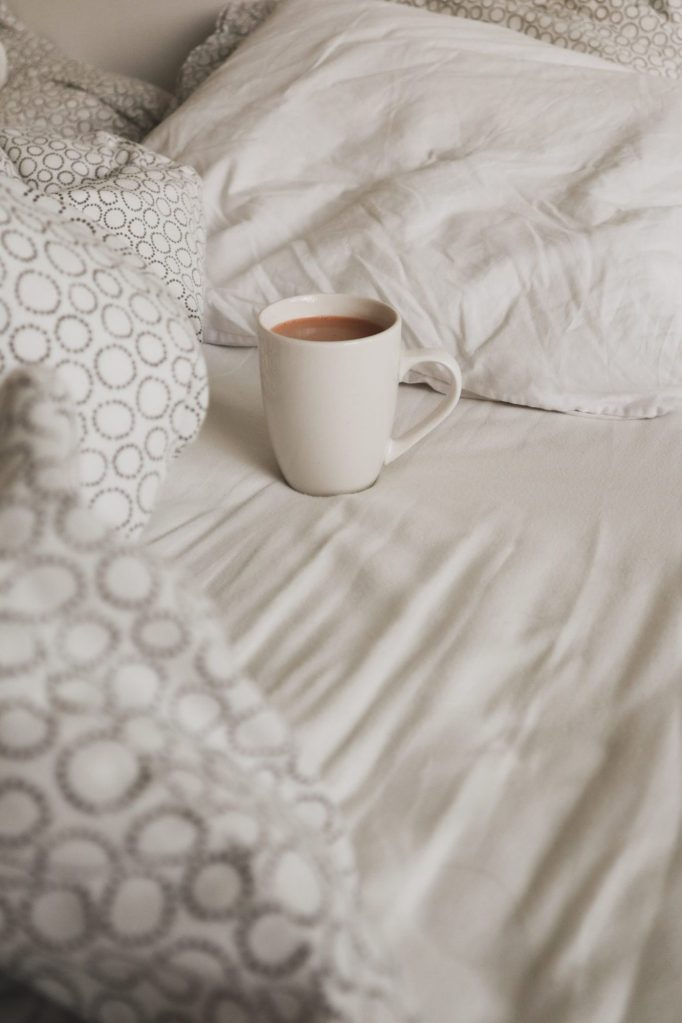 A white cup of coffee, resting on a bed covered in white and grey bedding.