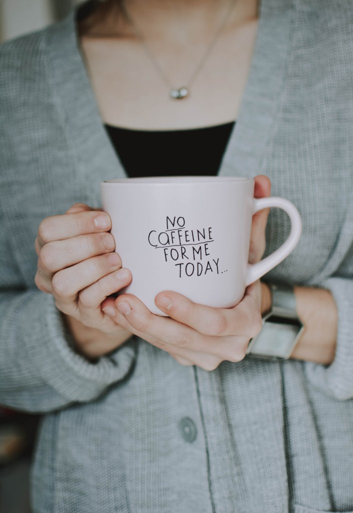 """Woman in a knitted cardigan holding a mug saying """"no caffeine for me today"""""""