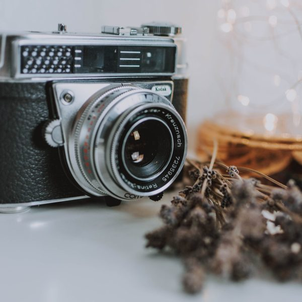 old fashioned camera on a white table, with fairy lights and dried flowers next to it