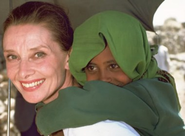 UNICEF Goodwill Ambassador Audrey Hepburn smiles as she carries a child on her back, under the shade of an umbrella, in the town of Mehal Meda in the northern part of the province of Shoa. Ms. Hepburn was visiting a food distribution centre in the town.