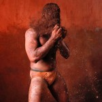 A wrestler rubs his hands with mud to prevent slipping due to sweat, during a traditional mud wrestling bout in Kolhapur