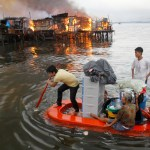 Residents paddle their makeshift boat to safety as fire engulfs houses at a slum community in Manila