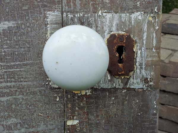 White porcelain door knob with rusty keyhole