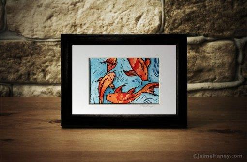 koi fish mono print shown in frame on desk