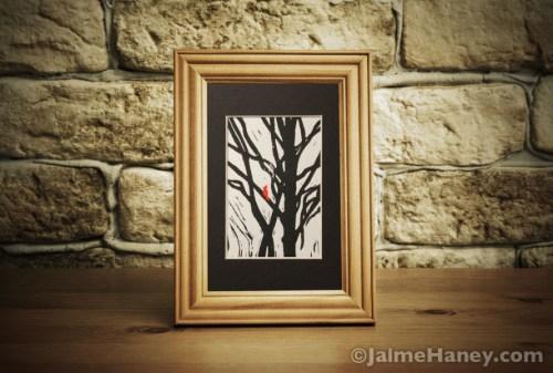 red-bird-black-tree,-blk-mat-shown-in-frame-on-desk
