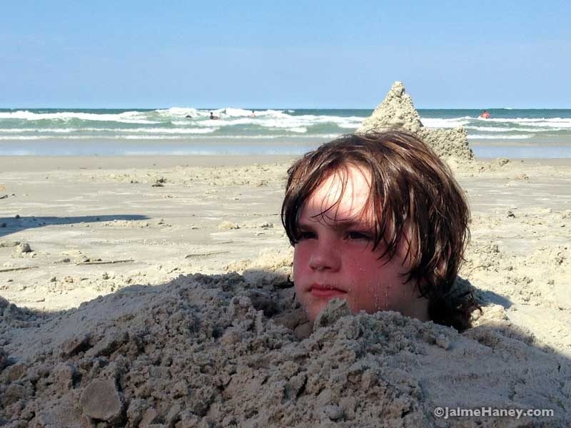up to his neck in sand on a Florida beach