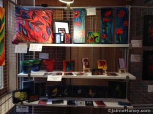 Shelves full of small paintings in the art booth of Jaime Haney at Christmas in New Harmony