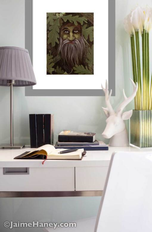 A green man painting matted print shown in a desk area setting on the wall.