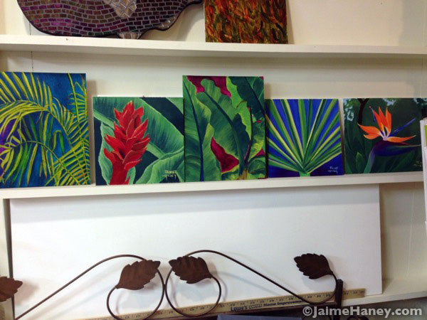 A shelf of five tropical paintings by Jaime Haney