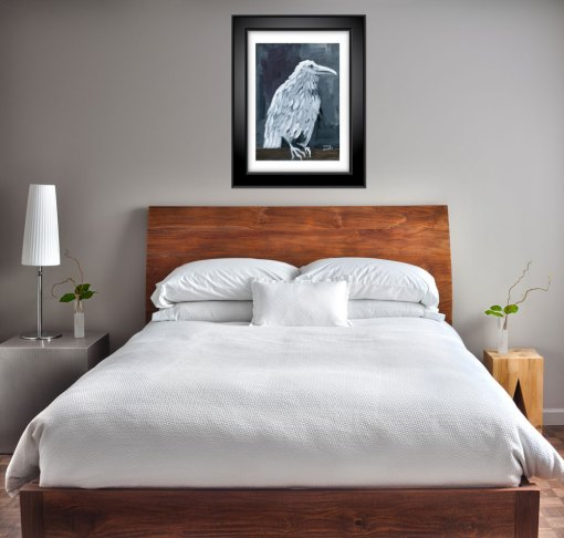 white raven print shown matted and framed over a bed