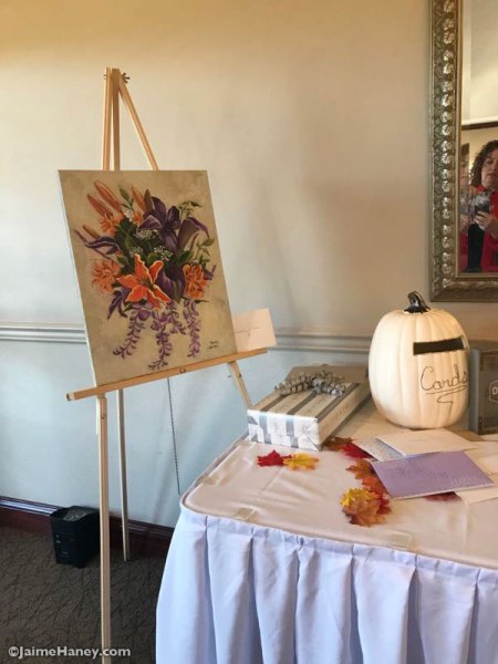Bridal bouquet painting on easel at gift table