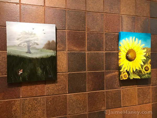 Fox in a meadow painting and  sunflowers painting shown by Jaime Haney at the October Alexandrian Public Library Art exhibit.