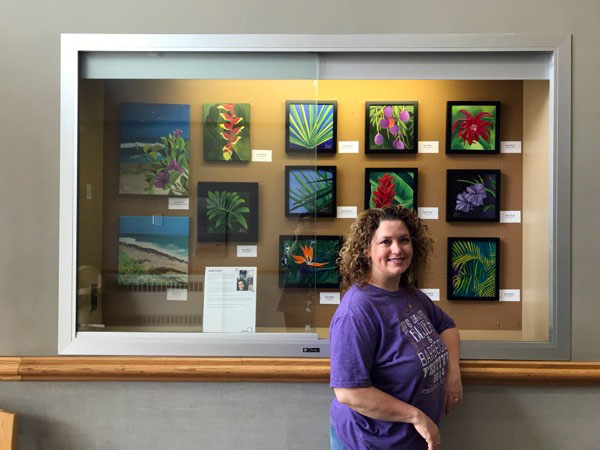 Jaime Haney with her paintings in front of the case
