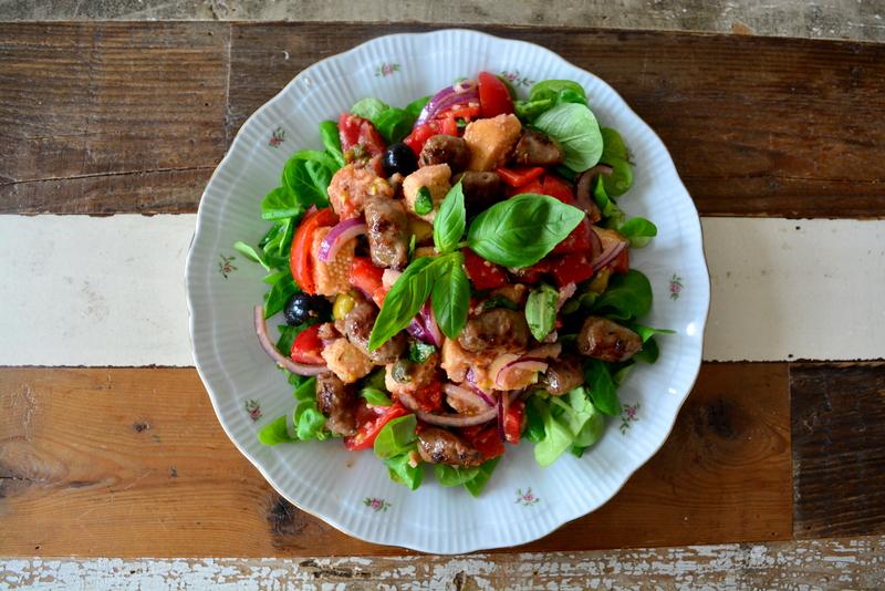 Italiaanse Panzanella met worst, tomaat, geroosterde paprika, basilicum, rode ui, ciabatta, rode wijn azijn, kappetjes, olijven