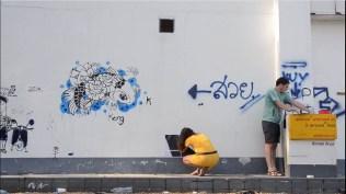 On colle des affiches dans la rue, à Chiang Mai !