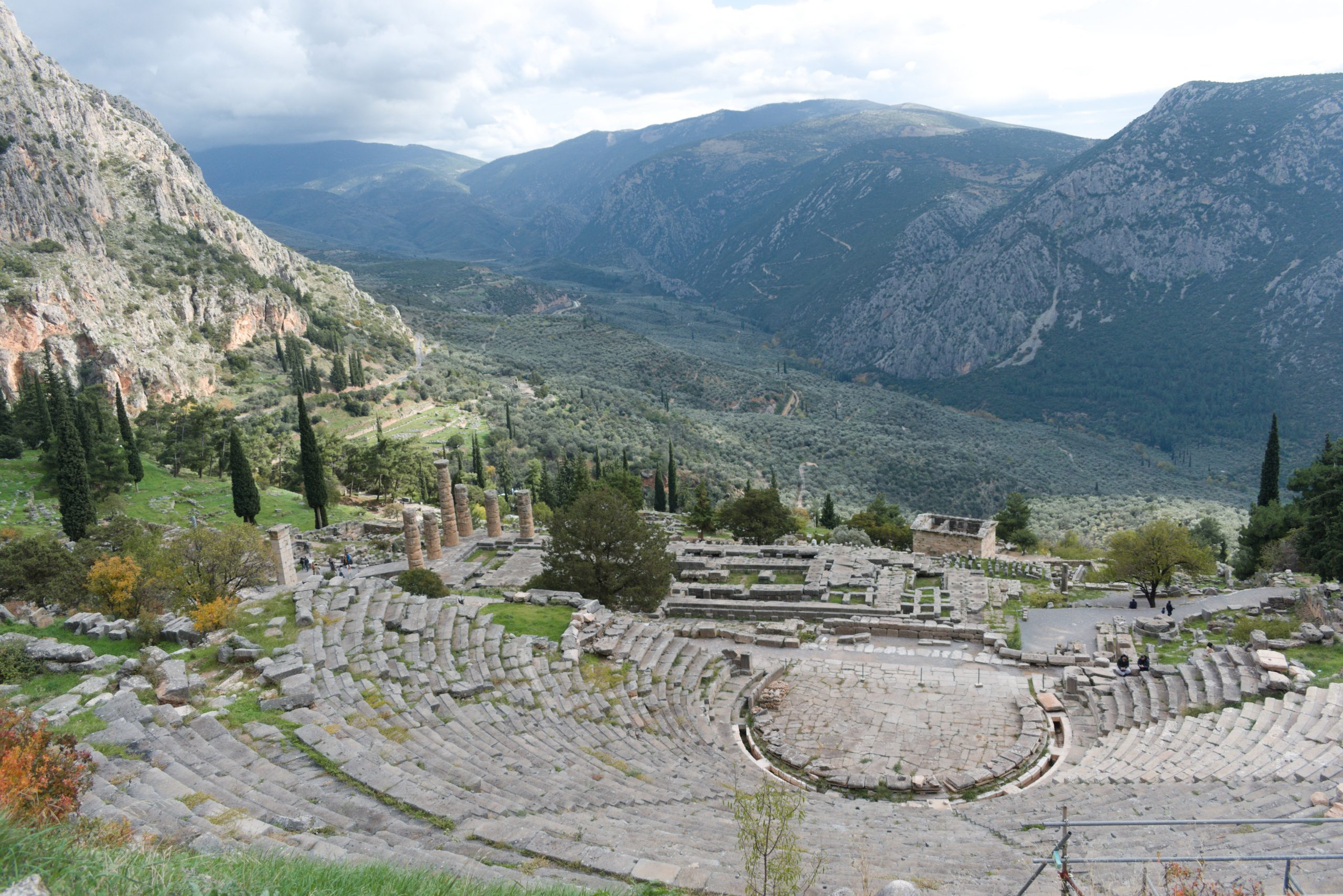 The Temple of Apollo in Greece surrounded by green mountain and field