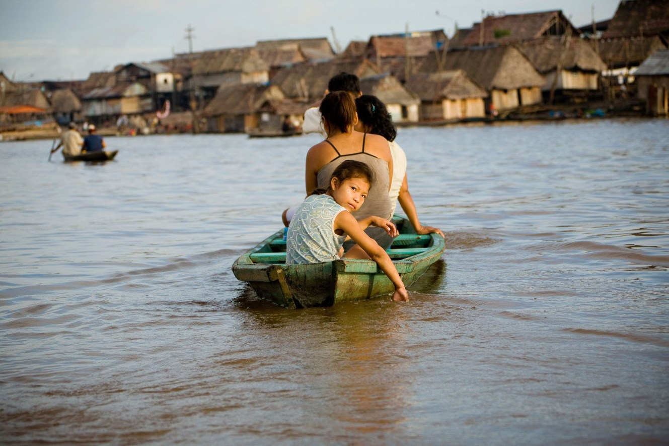 A girl crosses the Itaya River in Iquitos, Peru, by riverboat taxi.