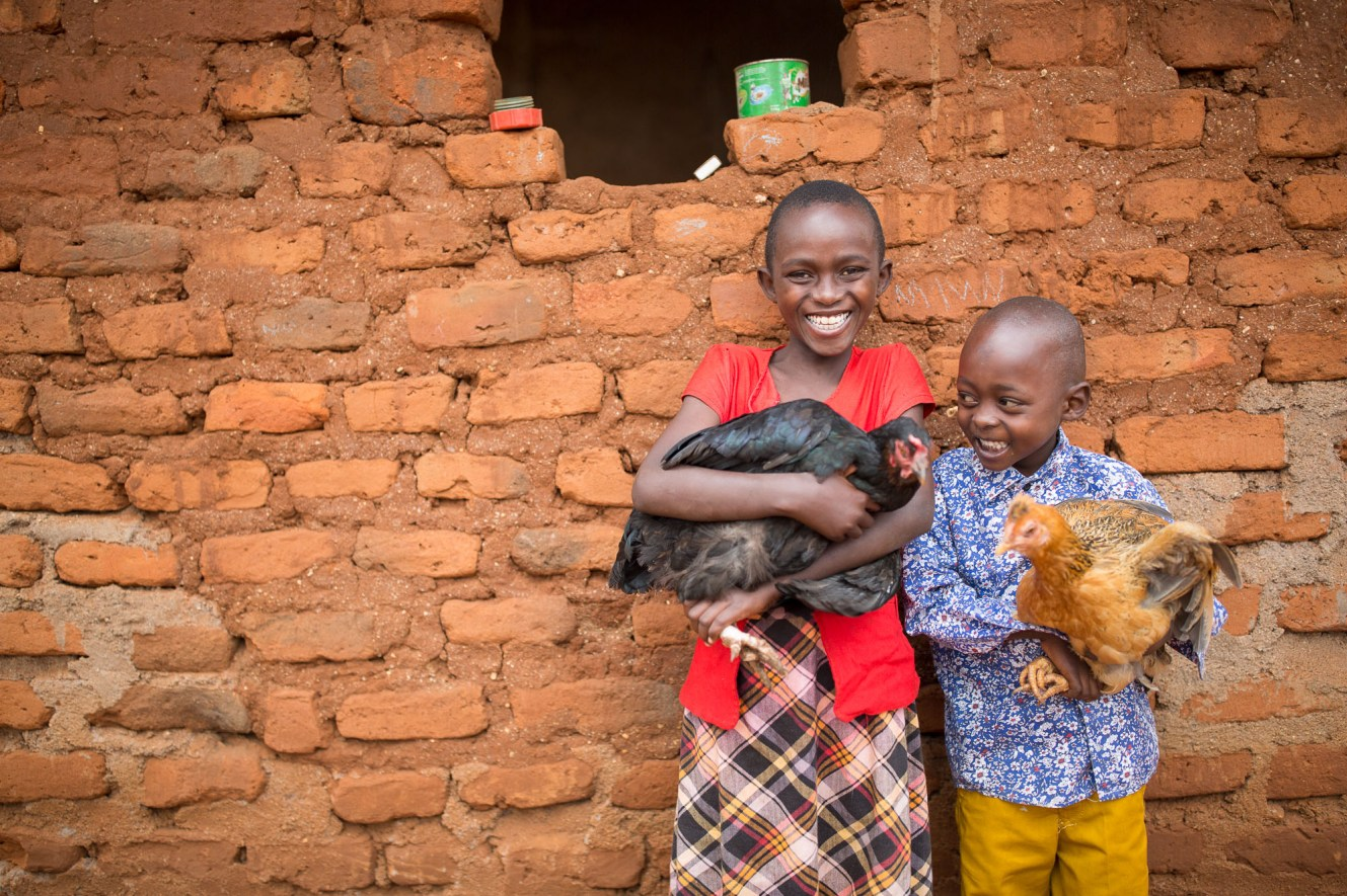 Nduku (10) and her brother Muthiani (6) hold chickens at their home in Makueni County, Kenya.