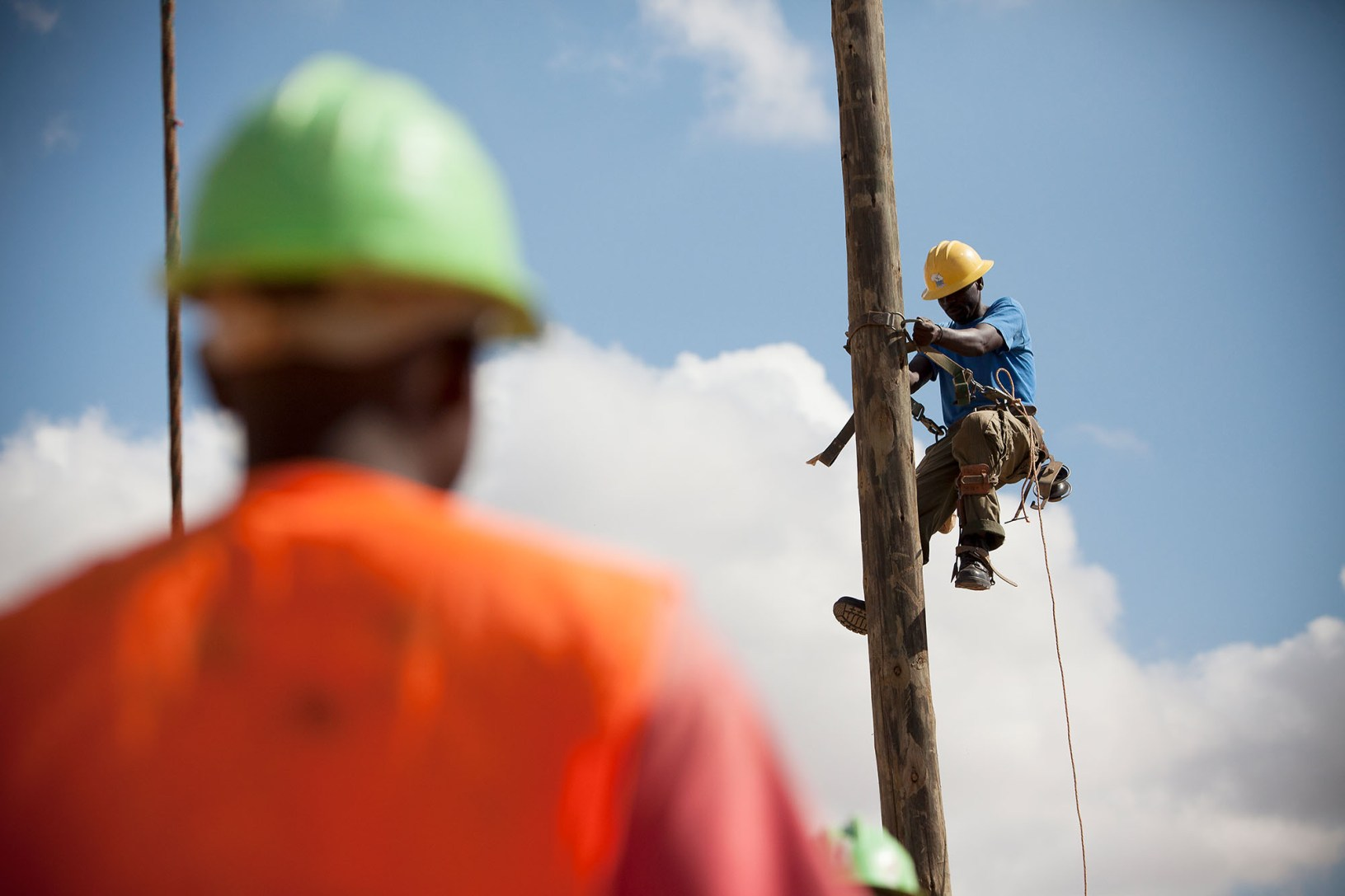 Workmen bring electrical lines to rural Tanzania for the first time.