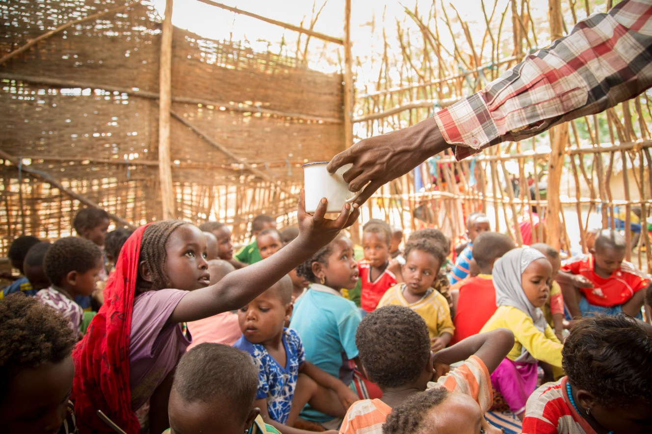 Misra (6) receives a cup of water after mealtime at a ChildFund-supported early childhood development center in Fentale District, Ethiopia.